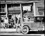 Untitled (group of Negro men in front of old store, car at right)