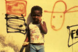 Child making fist in front of graffiti, Nicaragua