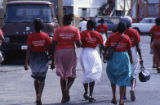 "Women walking with t-shirts: ""Education for People's Power Production and Defence,""..."