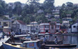 People in boats next to city street, Grenada