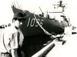 Phil Valdez standing in front of Navy ship