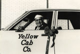 Harry E. Kinney in driver's seat of a taxi cab