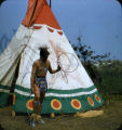 Plains American Indian performing hoop dance in front of dwelling
