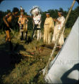 Group of Plains American Indians  in front of dwelling