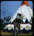 Plains American Indian in front of dwelling
