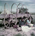 Two American Indian women working in front of wagon