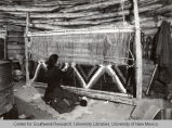 Navajo woman weaving on a loom