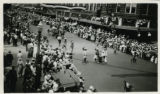 Photograph of Native American drummers followed by horse-drawn wagons during a 1922 parade in...