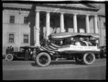 Photograph of a vehicle with a First in War, First in Peace sign during a 1922 parade in...