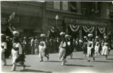 Photograph of Pueblo women walking with pottery on their heads during a 1922 parade in Albuquerque
