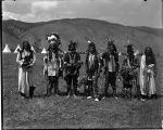 Plains Indian group standing with teepees in background