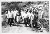 Ambassador Mari-Luci Jaramillo and accompanying journalists walk through a village with the...