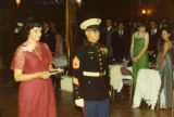 "Ambassador Mari-Luci Jaramillo, escorted by a Marine after receiving a piece of the ""birthday..."