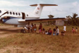 Villagers from Puerto Lempira under the Embassy plane's wing looking for shade
