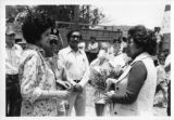A woman presents  Ambassador Mari-Luci Jaramillo a bouquet of calla lilies in La Esperanza,...
