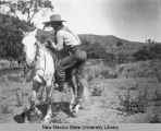 Man mounting a light-colored horse