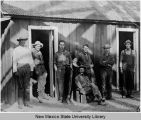 Seven miners standing by change house at Santa Rita Shaft