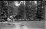 Group of riders outside cabin in mountains, New Mexico