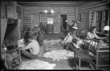 Group around fireplace in log cabin, New Mexico