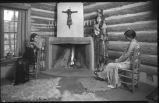 Women in log cabin interior, New Mexico