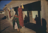 Pueblo woman with chili ristras, New Mexico