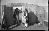 Unidentified woman in gateway at Isleta Pueblo, New Mexico
