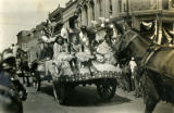 Girls ride on the back of a decorated wagon in the First American Pageant parade