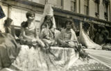 Rosie Brown and other girls in Mexican dresses ride on a float in the First American Pageant parade