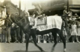 "Native American man rides a horse with blanket labelled ""The First American"" in parade"