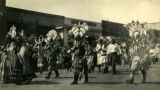 Native American men and women walk in the First American Pageant parade