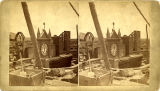 Walls of Saint Francis Cathedral being built around old church clock and bell tower, Santa Fe, New...