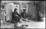 Interior of Tewa home with Hopi girl grinding corn, Moqui, Arizona