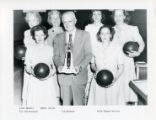 L. C. Becker holds a bowling trophy with a Womens bowling team.